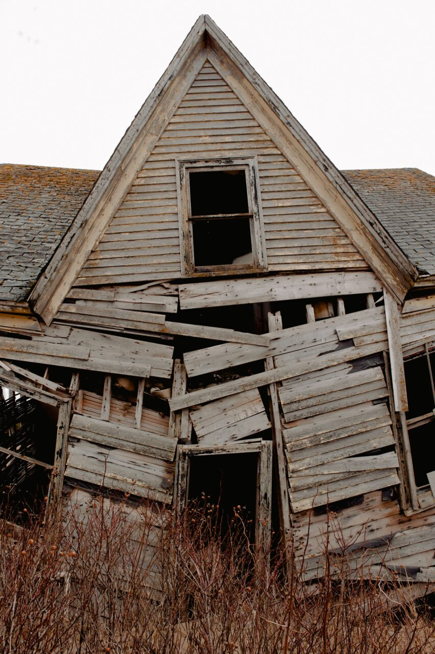 Photo is of a neglected and falling down wooden house.